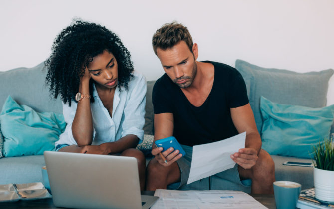 a young couple discussing refinancing student loan debt so, it doesn't ruin their retirement
