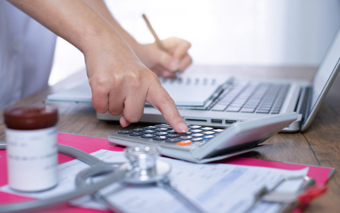 doctor creating a financial plan with a calculator, notebook, and computer