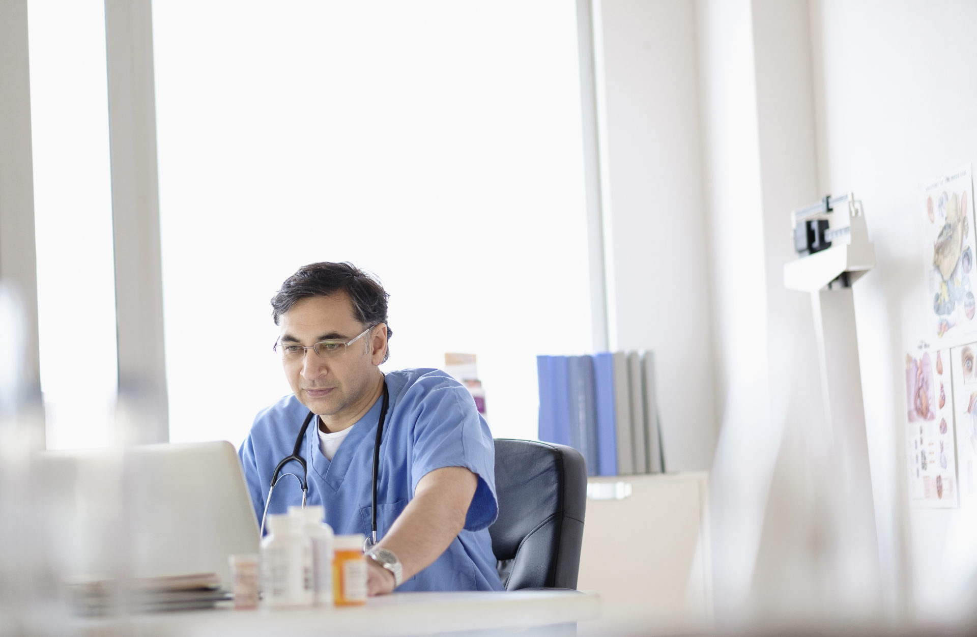 Mixed race doctor working on laptop